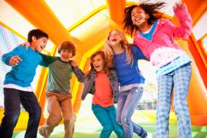 Kinder haben Spaß auf einer Hüpfburg
